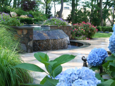 Heavy Dark stone spa contrasts the light and colorful planting around pool and travertine terrace