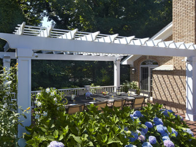 A large dining deck gets shade with a white stained cedar pergola.
