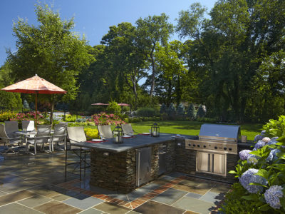 Stone veneered outdoor kitchen with stainless steel appliances and polished Pennsylvania bluestone counter.