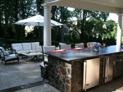 The outdoor kitchen under the cabana is further shaded from existing vegetation on site