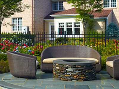 The stone veneer on the wood burning fire pit is repeated on both the raised spa and outdoor kitchen.