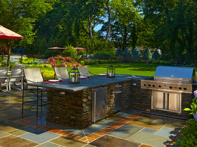 The outdoor cooking station has a bar counter with stools for casual dining or to keep the cook company.