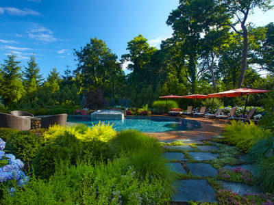 The bluestone stepping walk through overflowing gardens sets the tone for the natural oasis pool area that lies beyond.