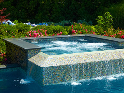 Glass tile on the raised spa shimmers in the sunlight.