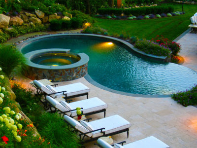Irregular shaped pool is squared off into slope with the travertine terrace and boulder wall planting