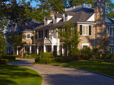 Antique cobblestone driveway enhances the old world design aesthetic of the homes architecture.