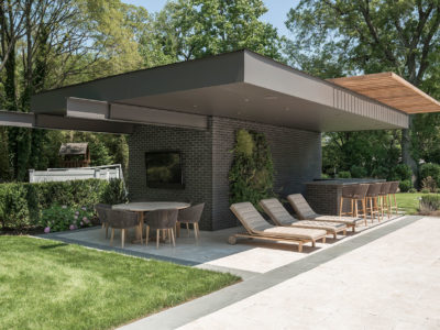 Charcoal brick poolhouse on travertine terrace with bluestone border and covered seating