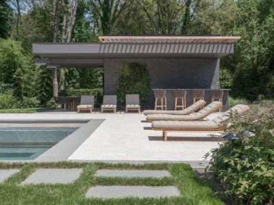 Stone steppers in grass leading to travertine terrace and cabana