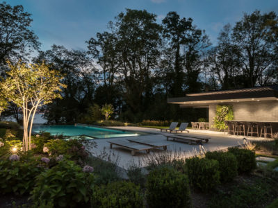 Modern pool at night with underlit cabana ceiling