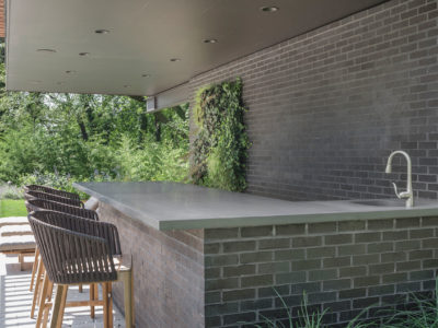 Charcoal brick outdoor kitchen with bluestone countertop around lush planting