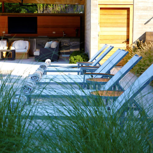 Board form concrete walls repeat surface details from the modern pool cabana.