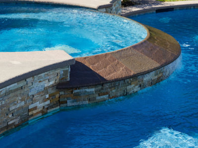 Heavy stone spa infinity edge cascading into pool